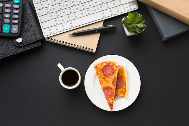Flat lay of desktop with keyboard and pizza