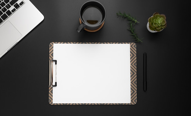 Flat lay of desktop with notepad and cup of coffee