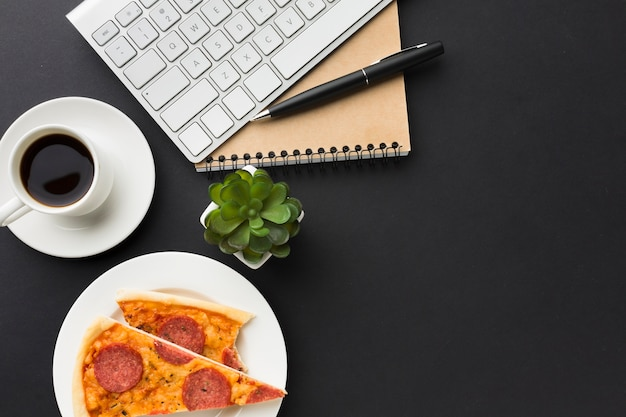 Flat lay of desktop with pizza and coffee cup