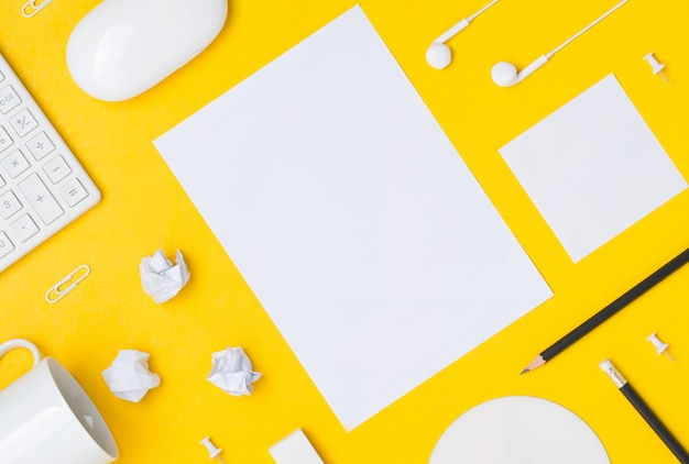 Flat lay of desktop workspace with blank space paper sheet on yellow background
