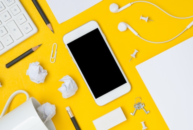 Flat lay of desktop workspace with blank space smartphone display on yellow background