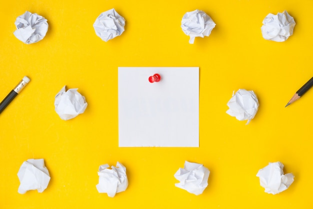 Flat lay of desktop workspace with red pushpin sticky on white paper noted on yellow background
