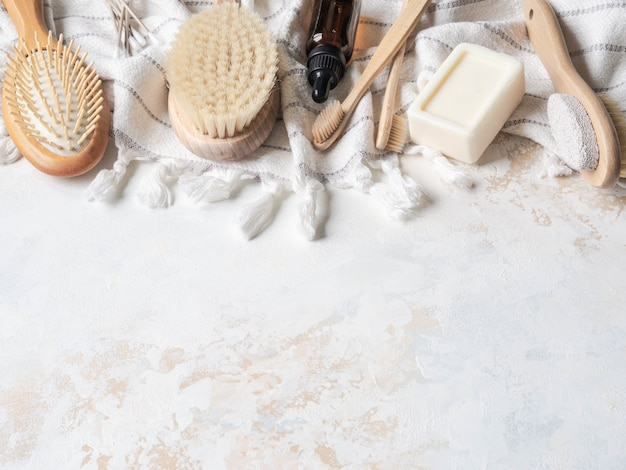 Flat lay different body brushes, white cotton towel, pumice, bamboo toothbrush, aromatic oil and a piece of soap. zero waste concept. eco-friendly bath set. top view