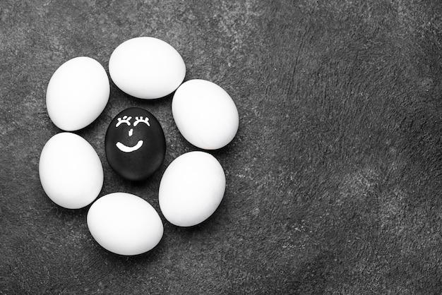 Lay piatto di uova di colore diverso con facce per vite nere importa movimento e spazio di copia