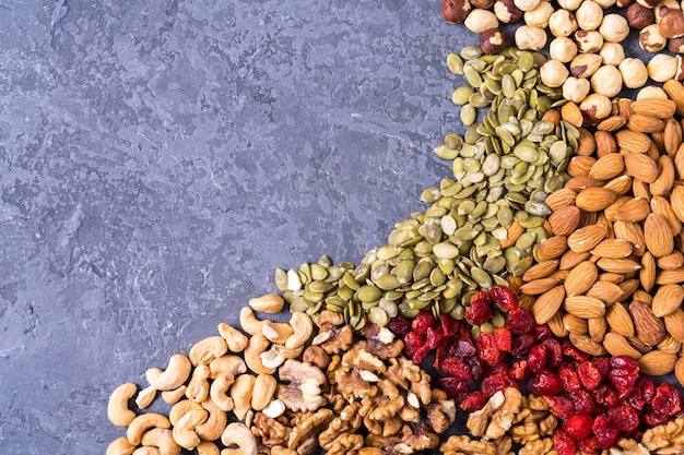 Flat lay different nuts on old wooden background.