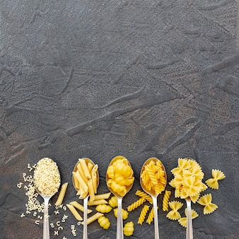 Flat lay of different types of pasta with copy space