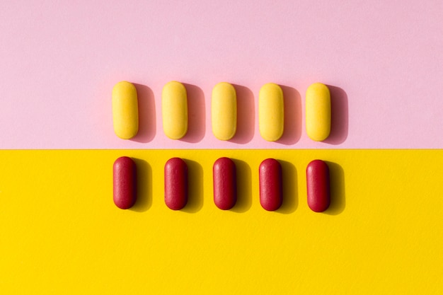 Flat lay of differently colored pills in rows