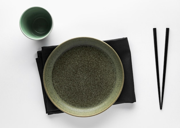 Flat lay of dinnerware with chopsticks and napkin