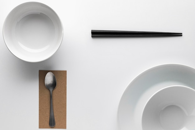 Flat lay of dinnerware with chopsticks and silver spoon