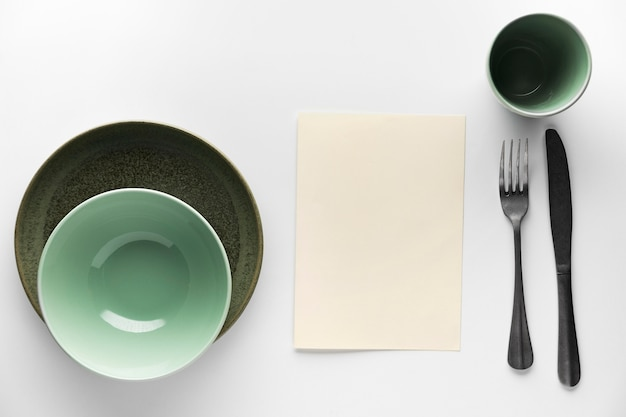Flat lay of dinnerware with silver cutlery
