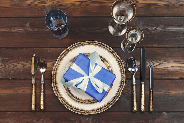 Flat lay of dishware and cutlery on wooden surface