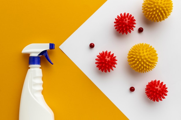 Flat lay of disinfectant bottle and viruses