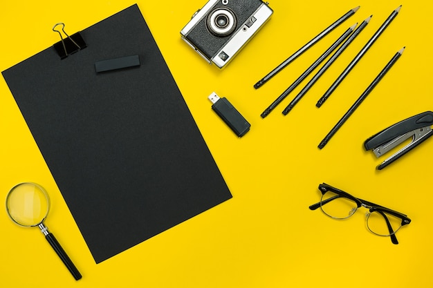 Flat lay display of business office gadgets with notepad, vintage camera, pen, develop, glasses and