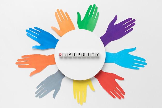 異なる色の紙の手でフラット横たわる多様性配置