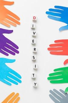 異なる色の紙の手でフラット横たわる多様性の品揃え