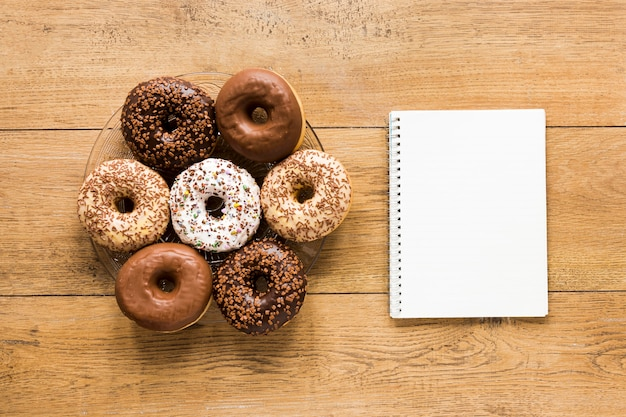 Flat lay of donuts on plate with notebook