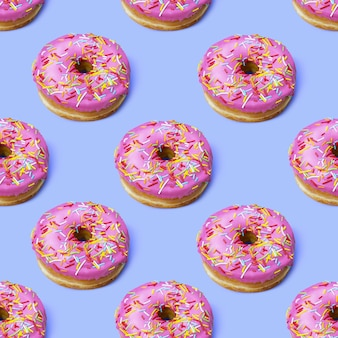 Flat lay donuts seamless pattern fashion minimalism style pink glazed donuts with colorful sprinkles