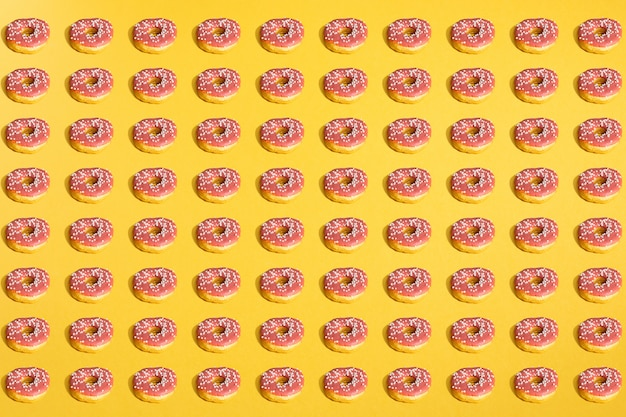 Flat lay of donuts and shadows pattern on yellow