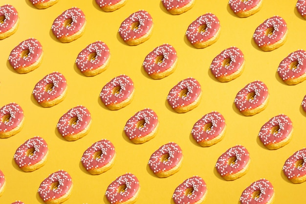 Flat lay of donuts and shadows pattern on yellow.