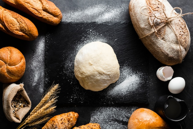 Flat lay of dough and bread on black background