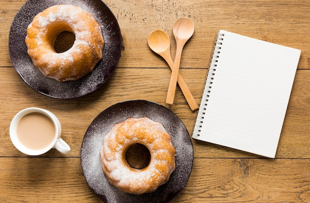 Flat lay of doughnuts on plates with notebook and wooden spoons