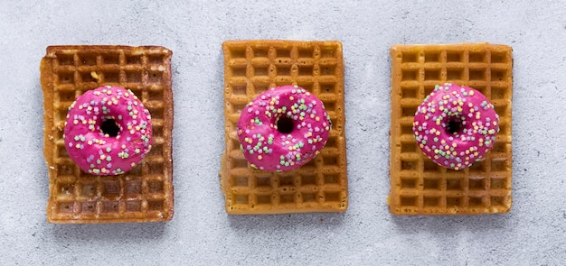 Flat lay of doughnuts on top of waffles