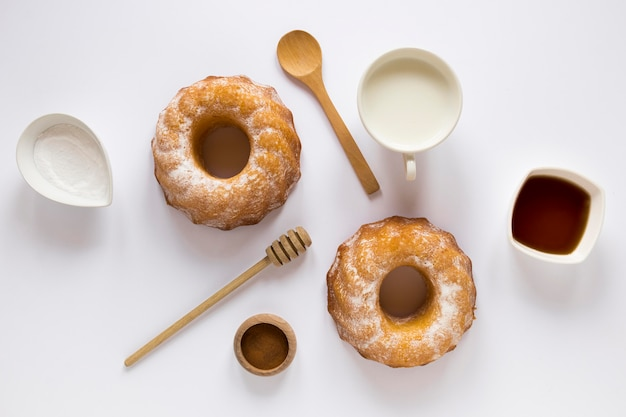 Flat lay of doughnuts with milk and honey dipper