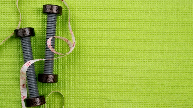 Flat lay dumbbells on green background