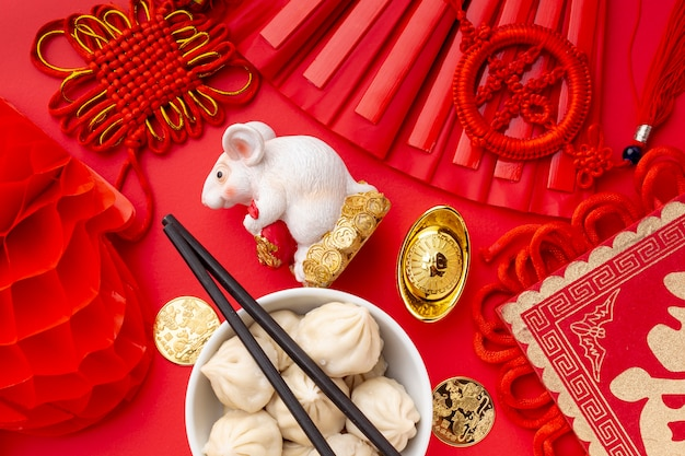 Flat lay of dumplings and rat figurine chinese new year