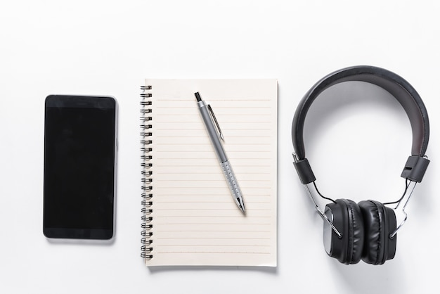 Flat lay of earphone, mobile phone and notebook on white background, music concept