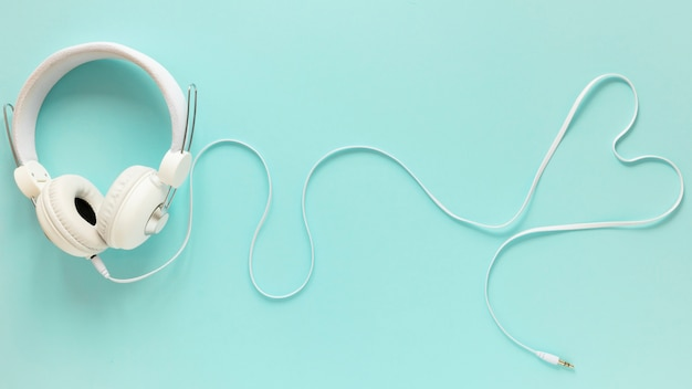 Flat lay of earphones on plain background