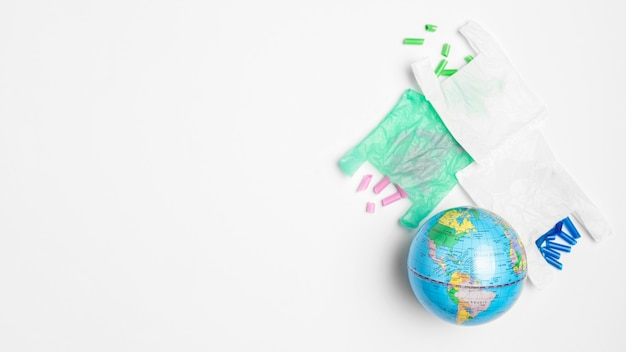 Flat lay of earth globe with plastic bags and copy space