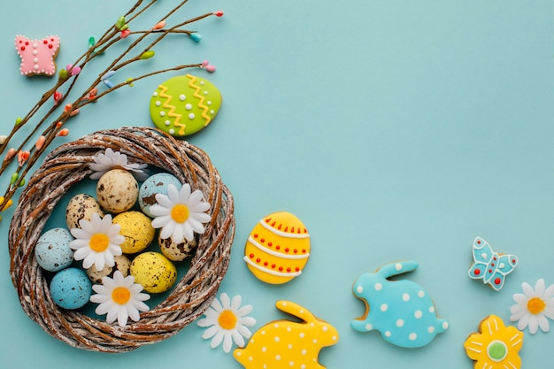 Flat lay of easter eggs in basket with chamomile flowers and bunny shape