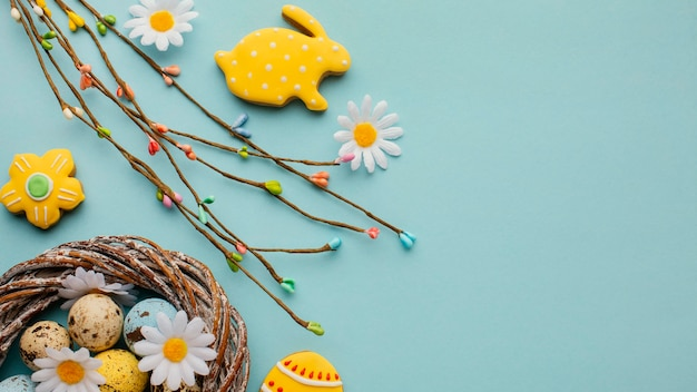 Flat lay of easter eggs in basket with chamomile flowers and bunny