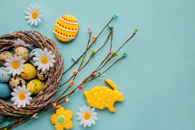 Flat lay of easter eggs in basket with chamomile flowers