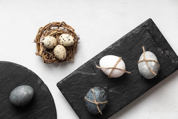 Flat lay of easter eggs in bird nest and slate
