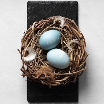 Flat lay of easter eggs in bird nest on slate