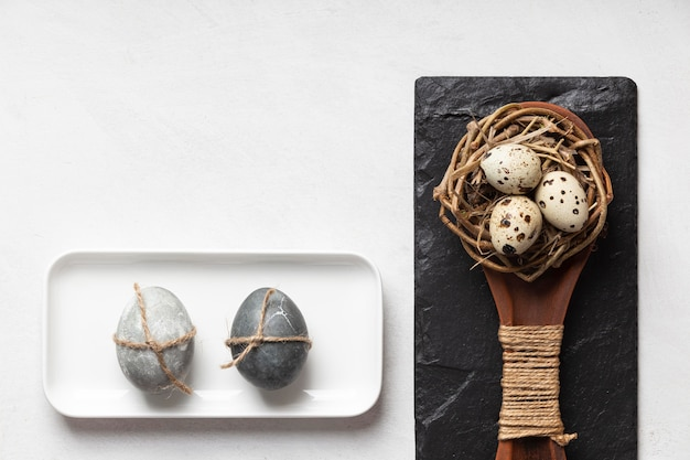 Flat lay of easter eggs in bird nest with slate and wooden spoon