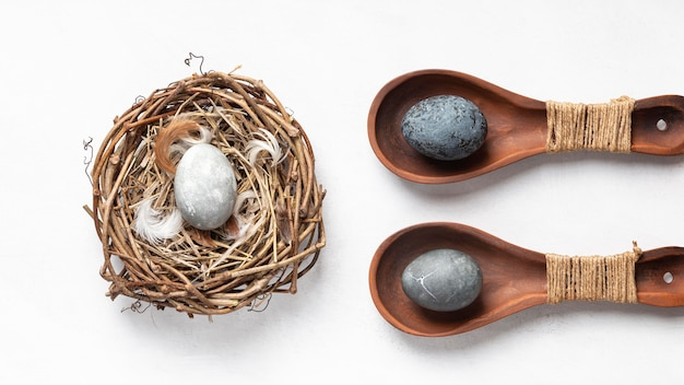 Flat lay of easter eggs in bird nest and wooden spoons