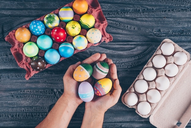Flat lay easter eggs in egg cartoon with man_s hands full of eggs on dark wooden background.