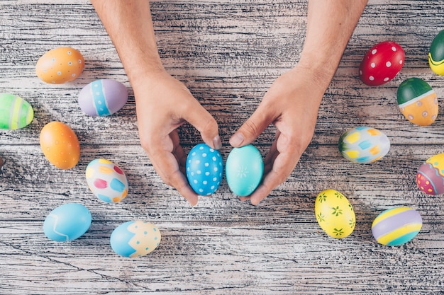 Flat lay easter eggs in man_s hands and on wooden background.