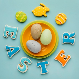 Flat lay of easter eggs on plate with bunny shape