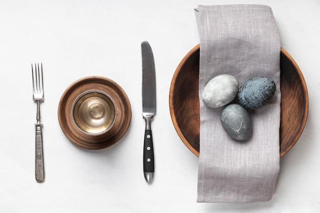 Lay piatto di uova di pasqua nella piastra con tessili e posate