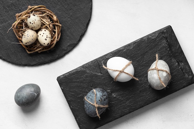Flat lay of easter eggs on slate and in bird nest