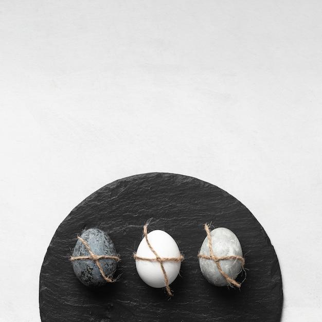 Lay piatto di uova di pasqua su ardesia con copia spazio