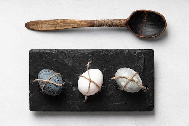 Lay piatto di uova di pasqua su ardesia con cucchiaio di legno