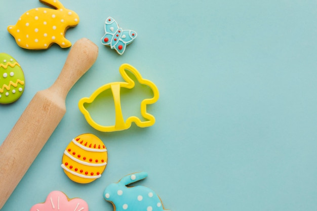 Flat lay of easter eggs with bunny shapes and rolling pin