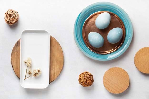 Lay piatto di uova di pasqua con piatti e fiori