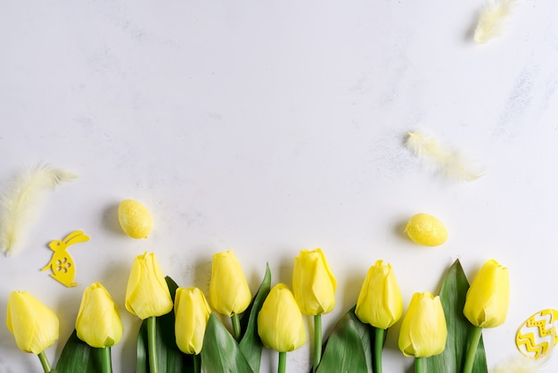 Flat lay of easter eggs with tulips on stone marble background