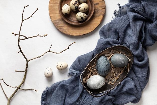 Lay piatto di uova di pasqua con ramoscello e tessile